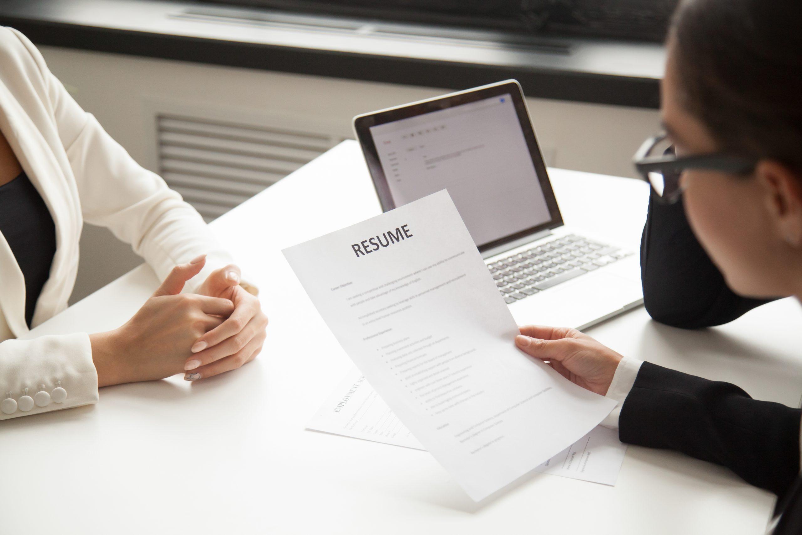 Rekruterka siedzi przy biurku i czyta CV kandydatki do pracy, która siedzi naprzeciwko
