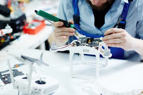 Closeup shot of unrecognizable man testing electric current in circuit board of disassembled drone using multimeter tool on table in maintenance shop