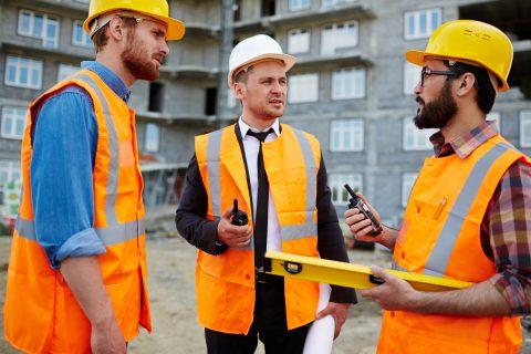 Trzej młodzi budowniczowie z walkie-talkie rozmawiający razem na placu budowy.