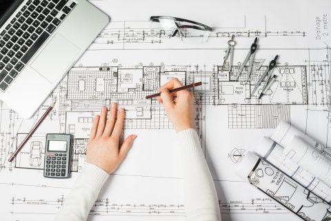 Kobiece dłonie kreślące ołówkiem po rysunku technicznym architektonicznym. Na dokumencie leży otwarty laptop, ołówek, kalkulator, cyrkle, okulary robocze oraz zwoje innych dokumentów.