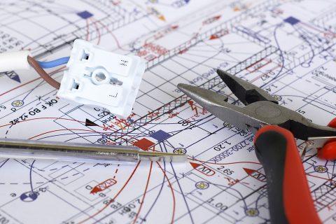 Na schemacie eklektycznym leżą kombinerki, miernik i gniazdko elektryczne.