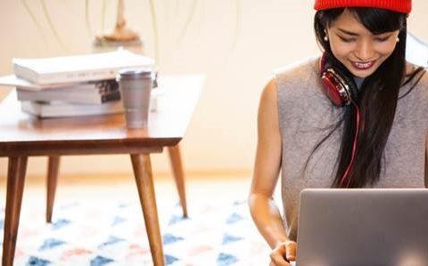 Kobieta siedząca w mieszkaniu przed laptopem, w tle stolik, na którym leżą przedmioty w rozmyciu.