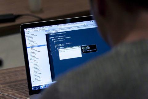 W kwadratowych kadrze fragment barku i głowy programisty oraz ekranu laptopa.