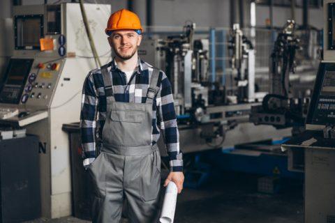 Z lewej na przodzie obrazka młody pracownik, mężczyzna w kasku pomarańczowym na tle maszyn w jakiej w fabryce.
