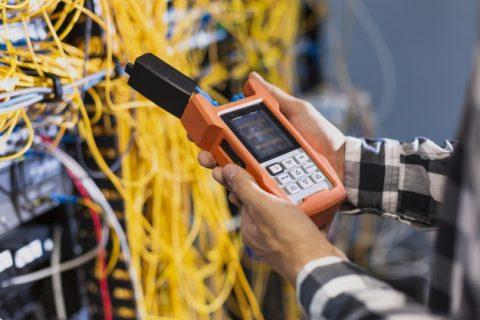 Na obrazku ręce młodego pracownika, mężczyzny, który trzyma miernik podłączony do sieci przewodów