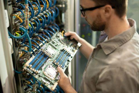 Na obrazku profil młodego pracownika, mężczyzny, który trzyma panel sterowania podłączonego do sieci przewodów w jakiejś pracy.