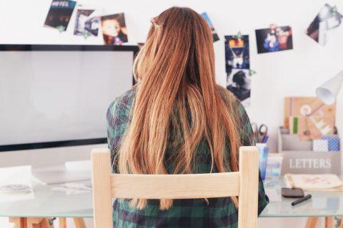 Dziewczyna z długimi ciemno blond włosami siedząca tyłem na krześle.