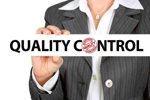 Kobieta trzymająca tabliczkę biała z napisem Quality Control