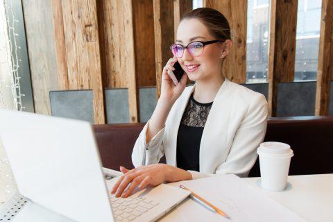 Asystentka projektanta podczas rozmowy telefonicznej, siedzi przed otwartym laptopem w biurze.