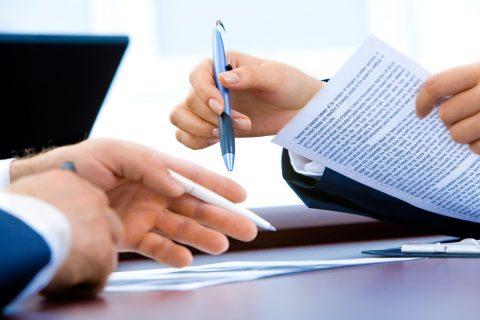 Dłonie mężczyzny po lewej z długopisem na tle dokumentów, obok po prawej dłonie kobiece również z długopisem trzymające CV.