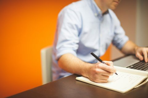 Mężczyzna siedzący przed laptopem, notujący coś w notatniku.