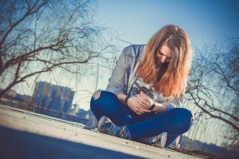 dziewczyna siedząca na chodniku w mieście i patrząca w smartfon