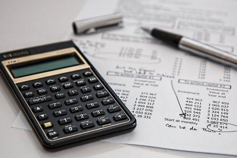 kalkulator, długopis i kartka z obliczeniami, które leżą na stole