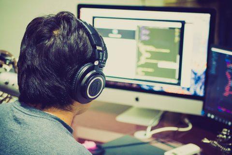 programowanie CNC na obrazku mężczyzna w słuchawkach pracujący przy komputerze