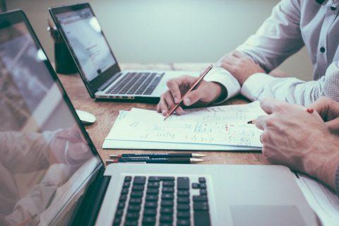 Dwa laptopy widoczne na biurku, a pomiędzy nimi notatki i dłoń pracownika, który analizuje dane z notatek
