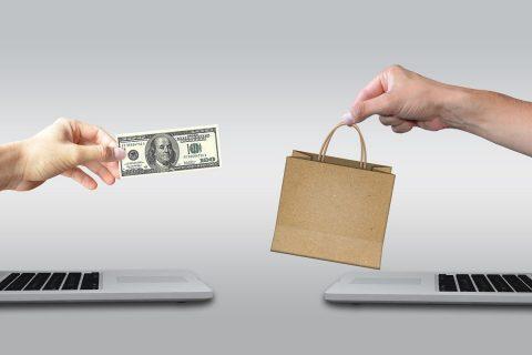 Jedna dłoń podaje banknot, druga w zamian torbę na zakupy nad otwartymi laptopami