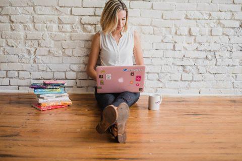 kobieta oparta o ścianę pisze coś na laptopie