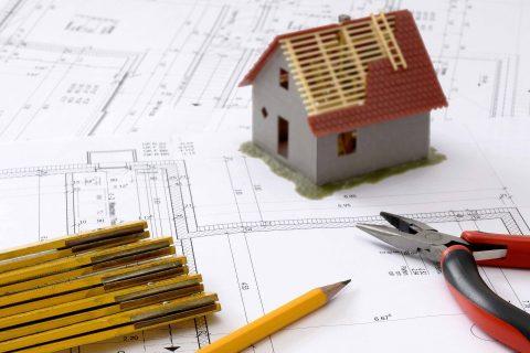 Model domku jednorodzinnego na kartce papieru z projektem, obok ołówki i kombinerki