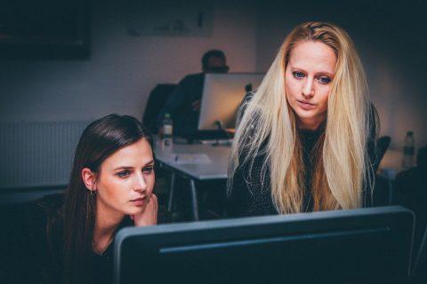 Dwie młode kobiety patrzą z uwagą w ekran komputera