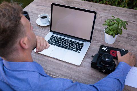mężczyzna pracuje przez laptopem, na biurku leży aparat fotograficzny, kwiatek, kawa