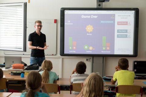 nauczyciel przy tablicy interaktywnej tłumaczy coś dzieciom