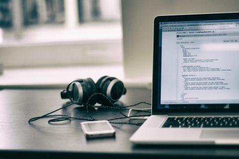 otwarty laptop z kodem na monitorze, obok niego leżą słuchawki i telefon