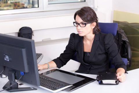 młoda kobieta w czarnym żakiecie przy biurku przed komputerem