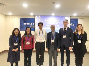 6 uczestników konferencji stoi przodem, pozuje do zdjęcia, w tle banery promujące konferencję