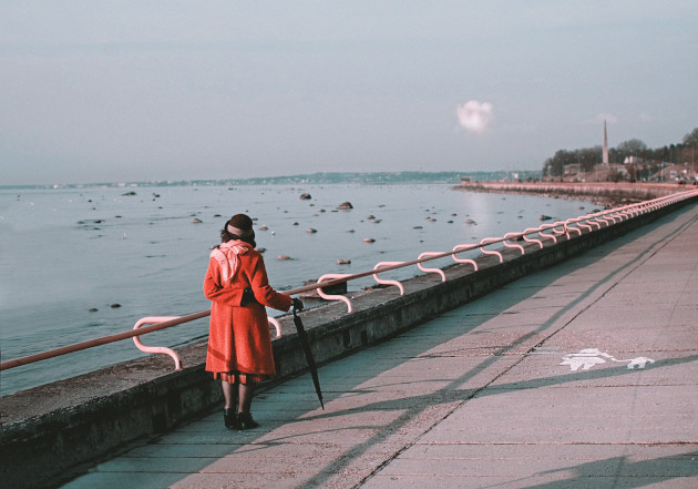Kobieta w czerwonym płaszczu, brązowym kapeluszu stoi w pogodny dzień na nadmorskim deptaku. Podpiera się parasolem. W tle po lewej morze, po prawej zabudowania przy deptaku.