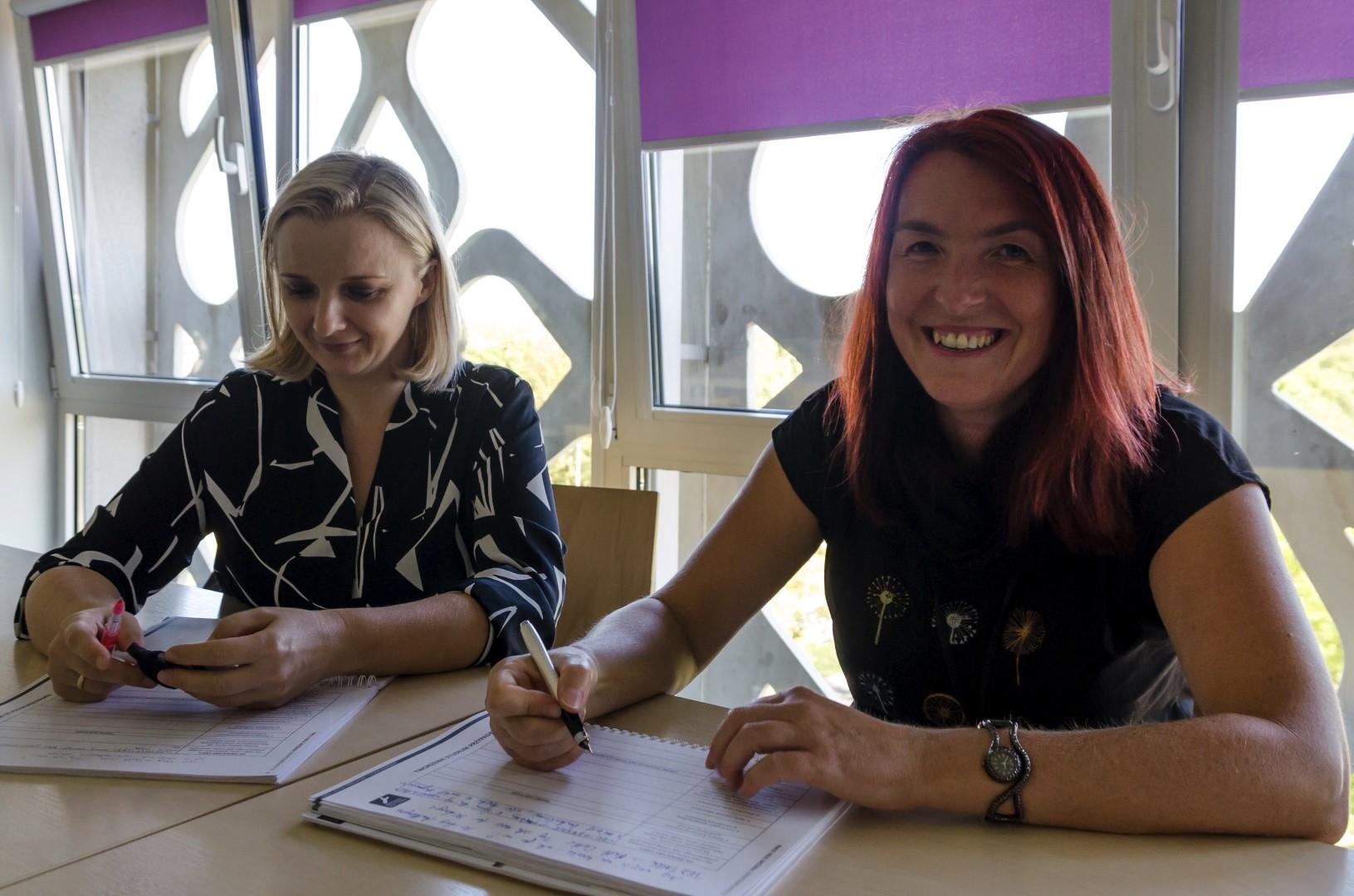 Dwie uczestniczki szkolenia siedzą przy biurku. Na biurku leża materiały szkoleniowe.