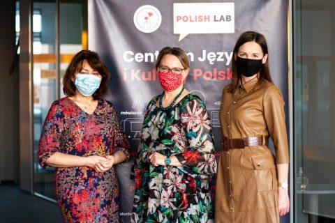 Trzy nauczycielki stoją w maseczkach na tle banneru z tekstem: Polish Lab Centrum Języka i Kultury Polskiej.