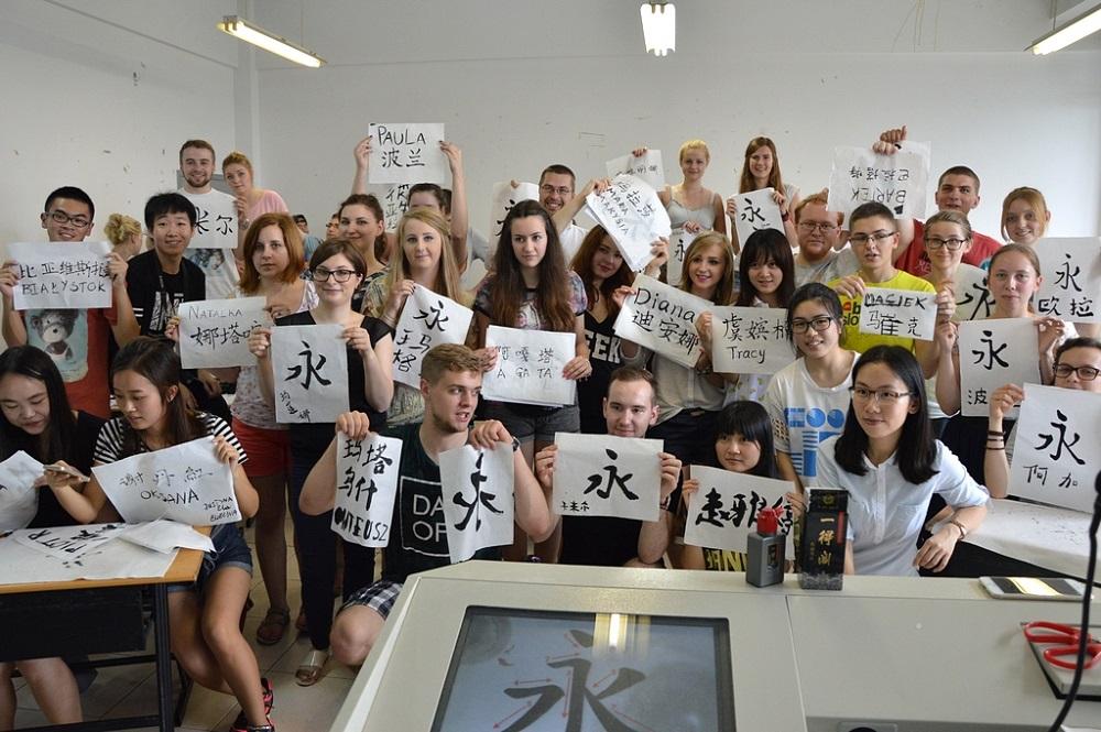 grupa studentów prezentująca kaligrafię chińską