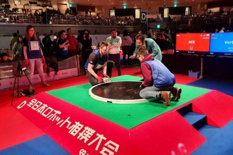 SumoMasters wystartowali na zawodach All Japan Robot-Sumo Tournament 2019 w Tokio. Zdjęcie przedstawia ring i studentów operujących robotami