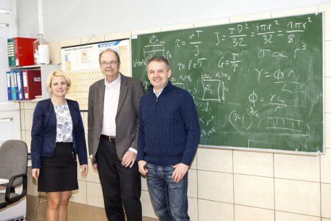 trzy osoby pozują na tle zielonej tablicy szkolnej w pracowni
