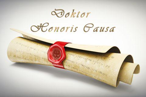 grafika przedstawia symboliczny dokument nadania tytułu doktora honoris causa zawinięty w rulon i opatrzony pieczęcią z czerwonego laku z wycisniętym logo Politechniki Białostockiej. Nad rulonem złote litery układające się w napis Doktora Honoris Causa