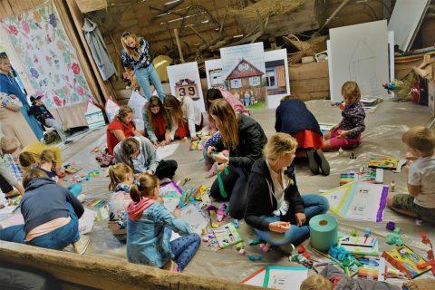 Grupa dzieci na warsztatach placuje w rozgardiaszu przygotowując projektu plastyczne