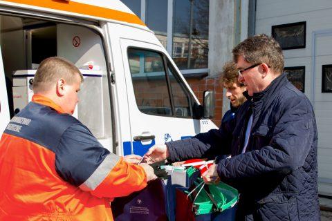 dwóch pracowników Wydziału Mechanicznego przekazuje ratownikowi medycznemu pakiety z przyłbicami medycznymi