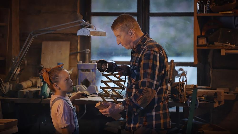 kadr z filmu promocyjnego Politechniki Białostockiej: dziadek pokazuje dziewczynce jak włącza się starą lampę