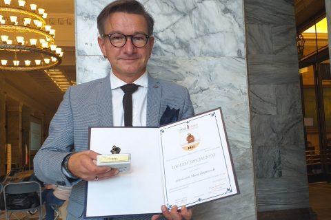 Fotografia. Portret Macieja Kłopotowskiego przezentującego dyplom i statuetkę Idola Specjalnego