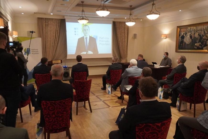 Podczas pierwszego spotkania Podlaskiej Regionalnej Rady Przemysłu Przyszłości grupa osób siedzi na sali obserwując wyświetlany na ekranie slajd