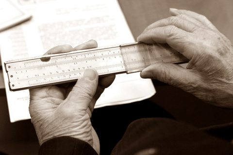 Fotografia w sepii. W rękach starszego mężczyzny widać suwak logarytmiczny