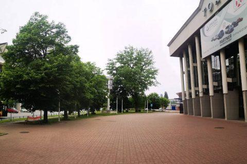 Zdjęcie przedstawia pusty plac przed halą Torwar, kilka drzew