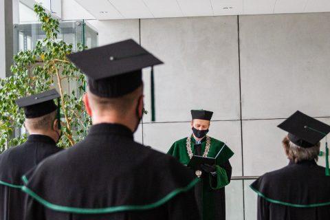 trzech mężczyzn w togach akademickich odwroconych tyłem w stronę odczytującego rotę przysięgi Prorektora Krętowskiego. Prorektor ma na twarzy maseczkę ochronną