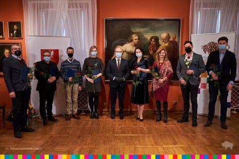 Sala w Muzeum Podlaskim w Białymstoku. Na zdjęciu stoi osiem osób, które odebrały stypendia artystyczne na 2021 rok. Wręczał je Marszałek Artur Kosicieki.